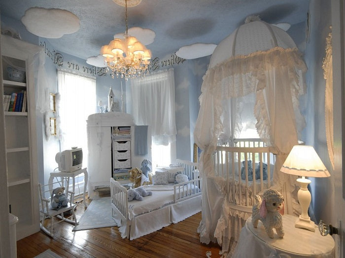 Sky and cloud themed nursery room with light blue walls and white furniture and bedding