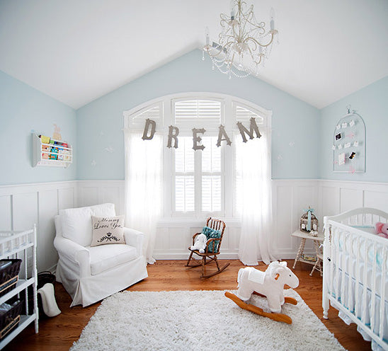 Light blue and white nursery, with white shuttters at the window, and the word Dream draped over the window