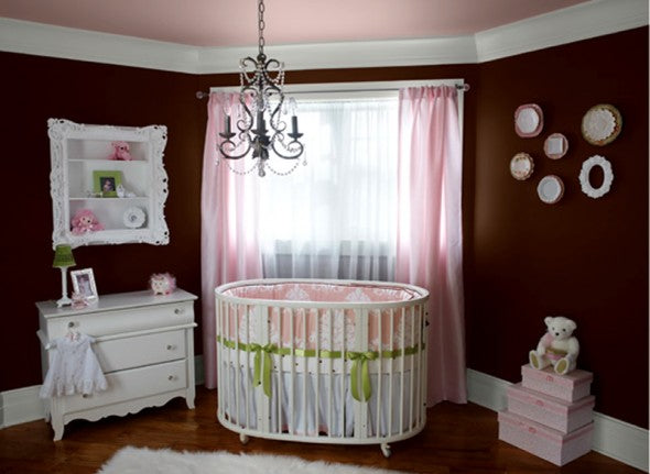 Dark maroon coloured nursery with pink curtains, white cot and other pink accessories in the room