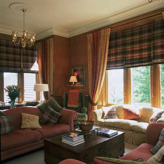 Red and cream living room with sofas and tartan roman blinds at the window