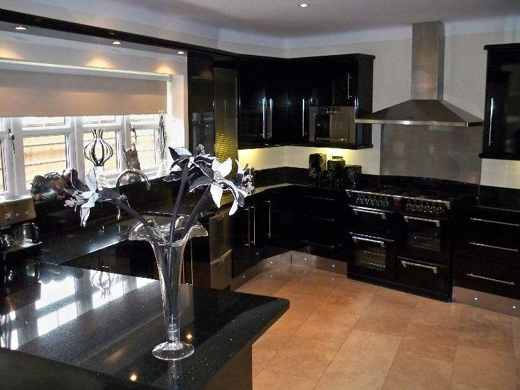 Kitchen with black units, white walls and beige tiled floor