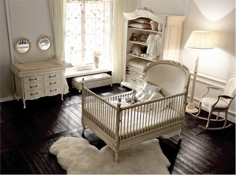 Beige and rich cream nursery with intricately carved cot on a dark wooden floor