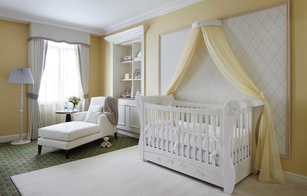 Yellow and white nursery with yellow canopy above a white cot