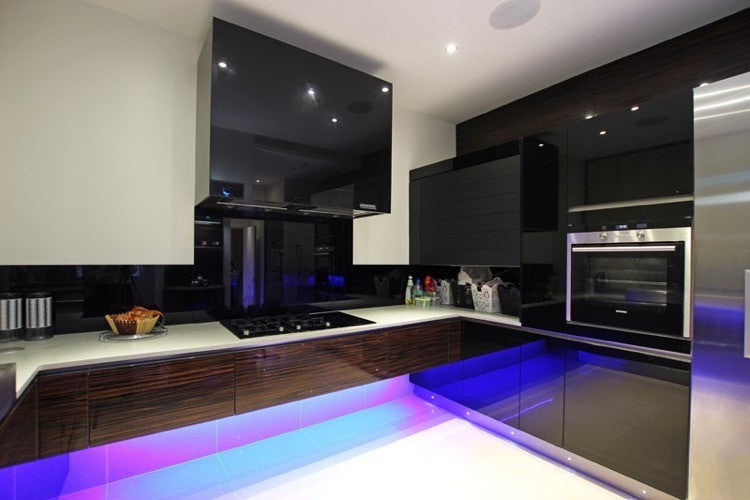 Black and white kitchen with blue and purple lighting under the counter tops