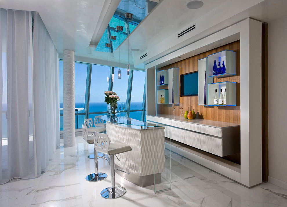Luxury penthouse apartment with white decor and home bar, with a view out at the ocean
