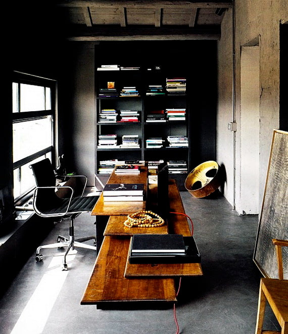 Rustic urban office with black shelves and stained wooden desks many of multiple wood panels