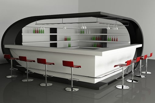 Large white and black home bar in the corner of a room, with red swivel chairs around the outside