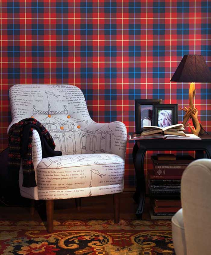 Red and blue tartan wallpaper, with a grey armchair next to a side table containing books