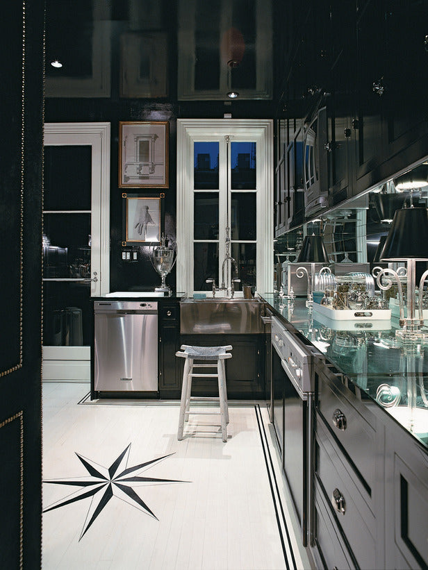 Black kitchen units and white tiled floor, with large compass style star design on the tiles