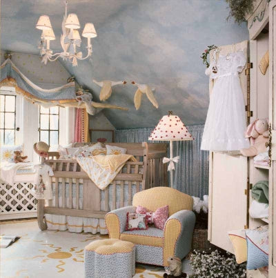 Countryside themed blue and white nursery, with beige cot and small blue and yellow kids armchair