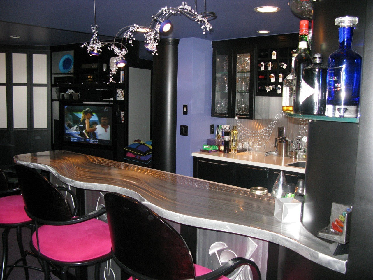 Contemporary home bar with silver and black surfaces, purple walls and pink and black swivel chairs