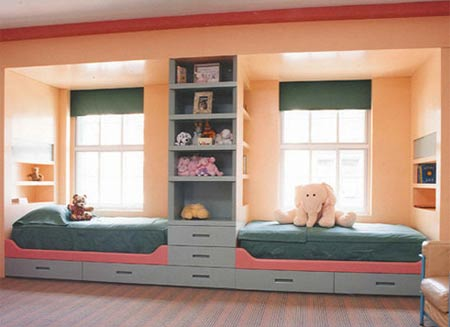 Beds under two different windows with a central column of shelves to separate them