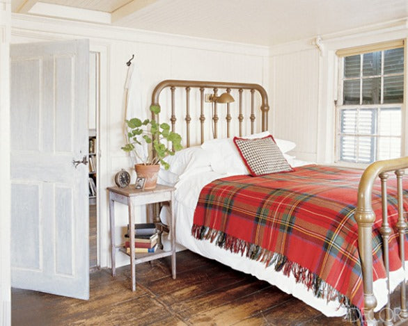 Red and green tartan plaid throw on white bedding, on a wooden bed frame