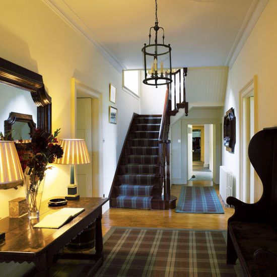 A wide hallway with tartan rugs on wooden flooring