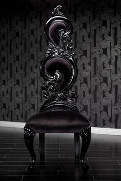 Black armchair with swirling back, on black floor tiles in front of black patterned wallpaper
