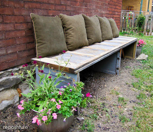 Outdoor garden bench made using old doors, topped with dark green cushions
