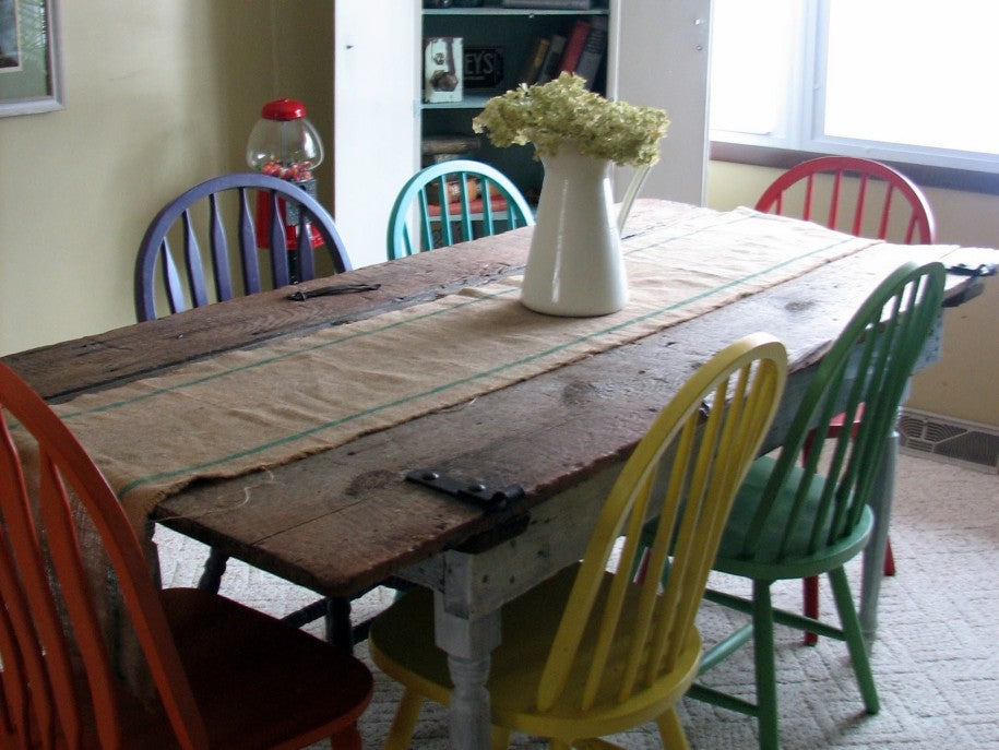 Colourful recycled chairs around a wooden table