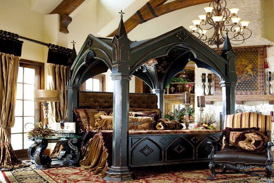 Stunningly Gothic four poster bed in black, with chunky wooden columns and a canopy like a cathedral roof