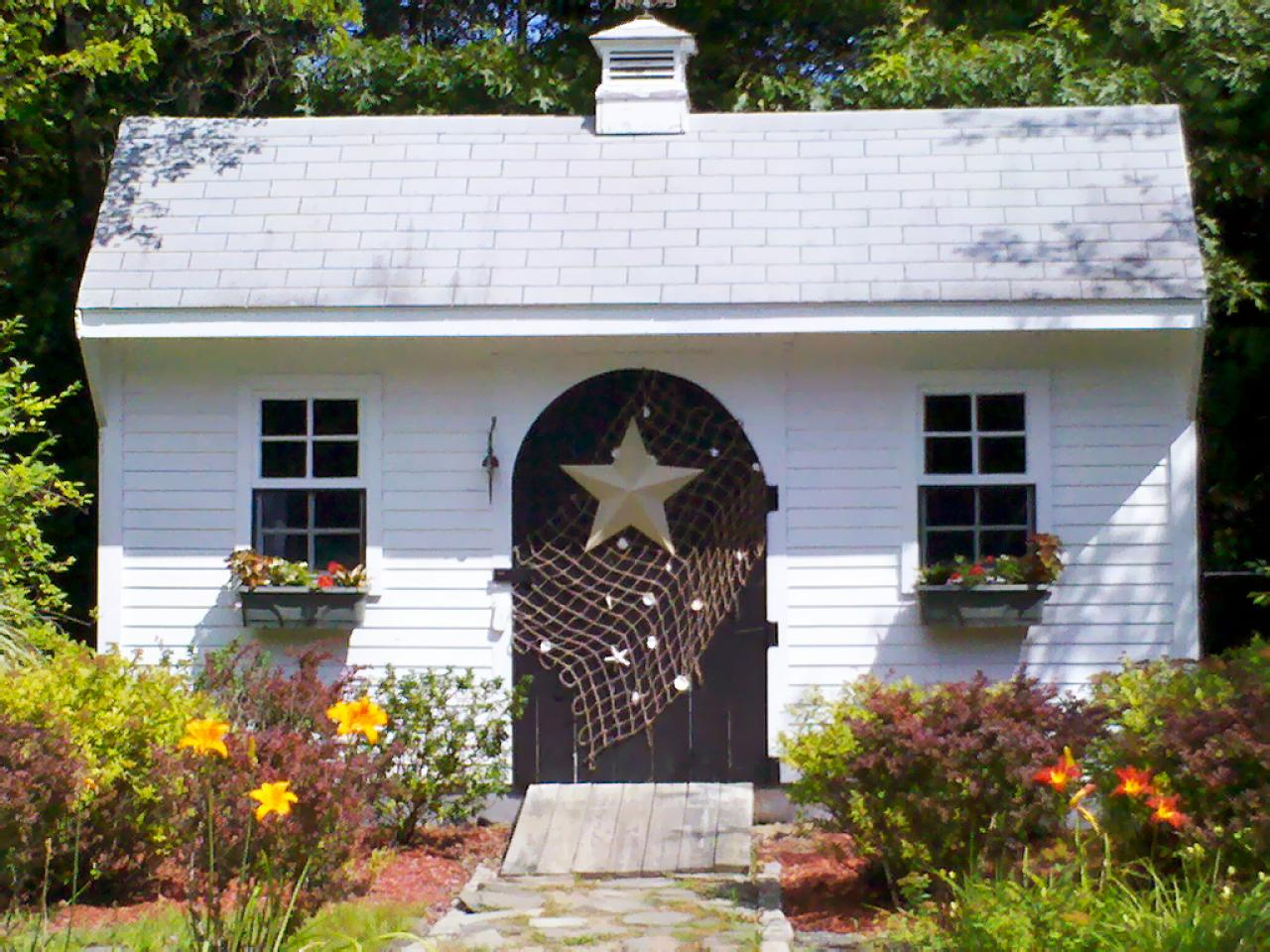Small white summer house with fishing net, shells and star fish on the front door