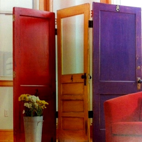 Old doors used to make a red, orange and purple privacy screen