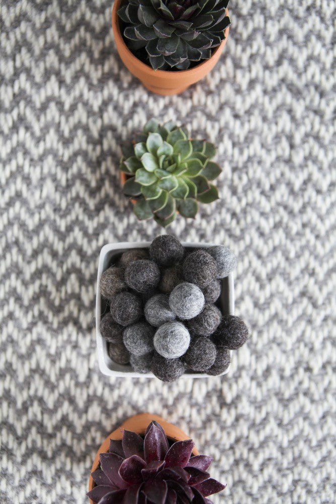 Plant pots with plants and a white pot containing grey felt balls