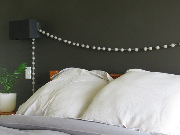 White felt balls draped on a dark green wall above a bed