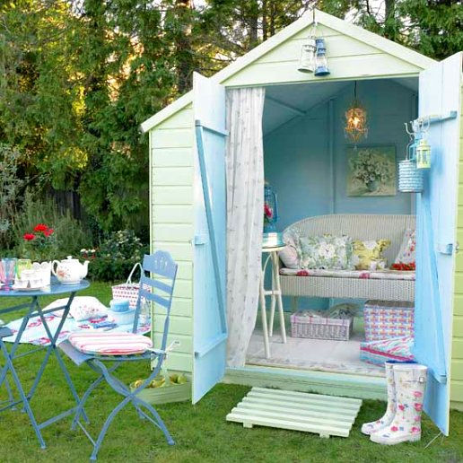 Pale green and light blue shed summer house with shabby chic furniture and accessories
