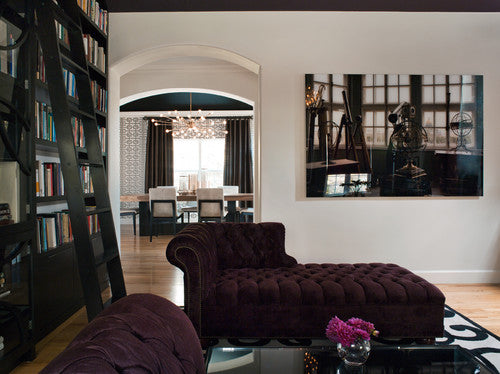 Contemporary living room with white walls and floor to ceiling black bookshelves