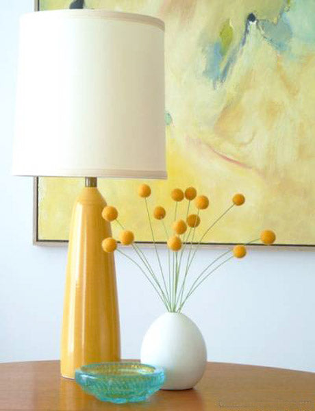 White vase filled with yellow felt balls on sticks, next to a yellow table lamp