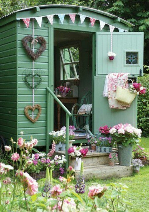 Green shed converted into a summer house, decorating with pink and blue bunting