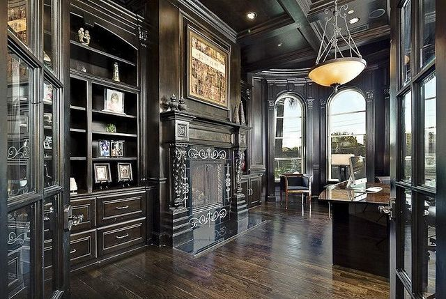 Gorgeous black Gothic home office, with stunning black finish wooden shelves, fireplace and desk