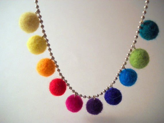 A metal chain ball necklace, with rainbow felt balls used to accessorise it