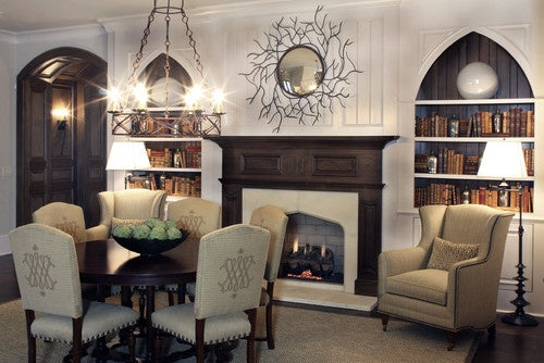 Modern Gothic decor with white walls, dark wooden fireplace and beige dining chairs and armchair