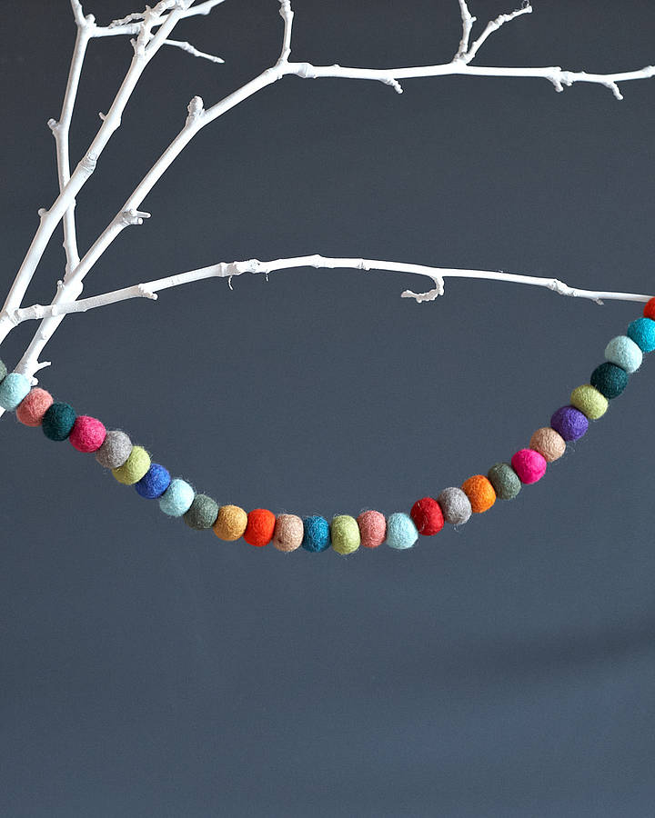 Multicoloured felt ball garland draped over a white branch