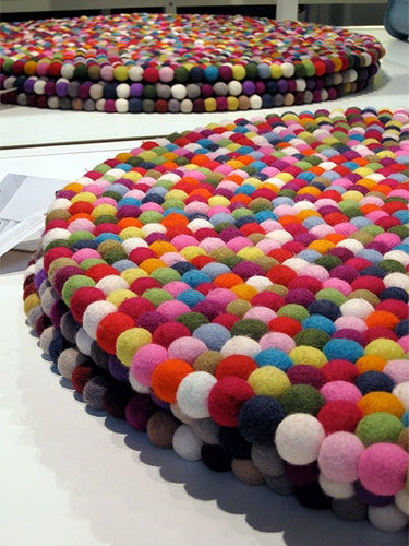 Large round multicoloured rug made from felt balls