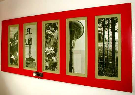 Recycled old door into a panelled red picture frame with multiple photos
