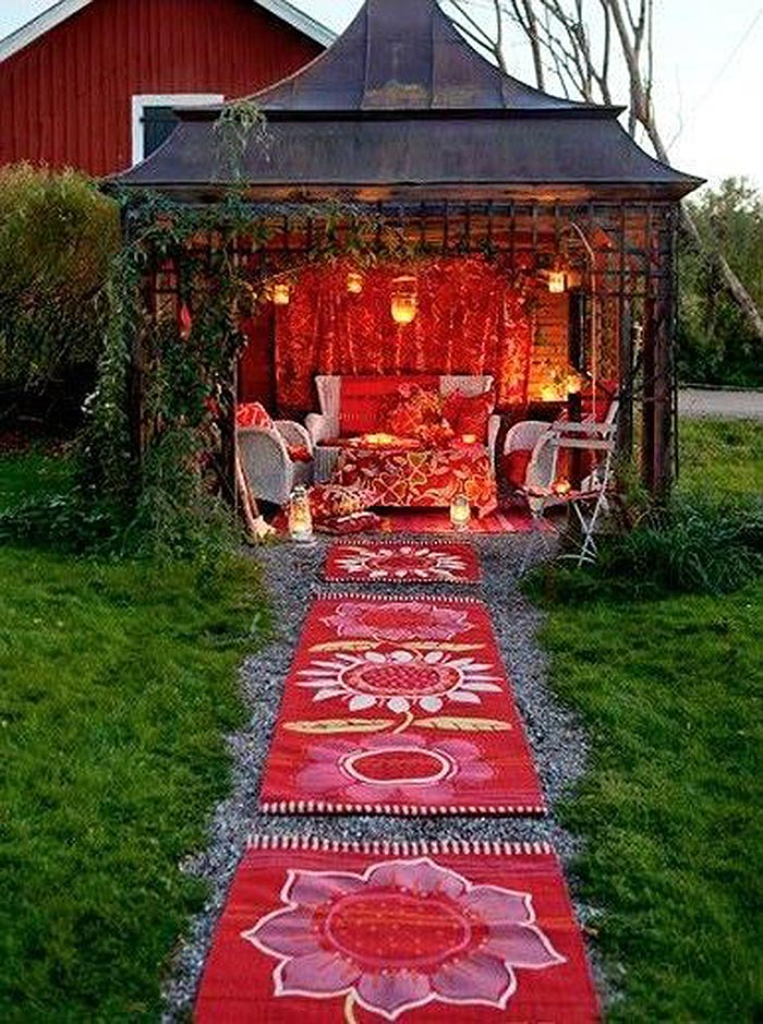 Outdoor cosy gazebo shed with red fabric interior and hanging lanterns