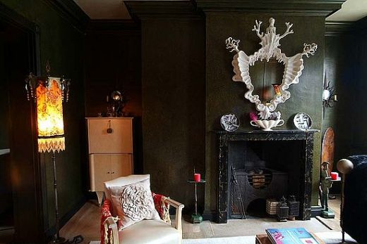 Very dark olive green walls with Gothic cream feature above the black fireplace