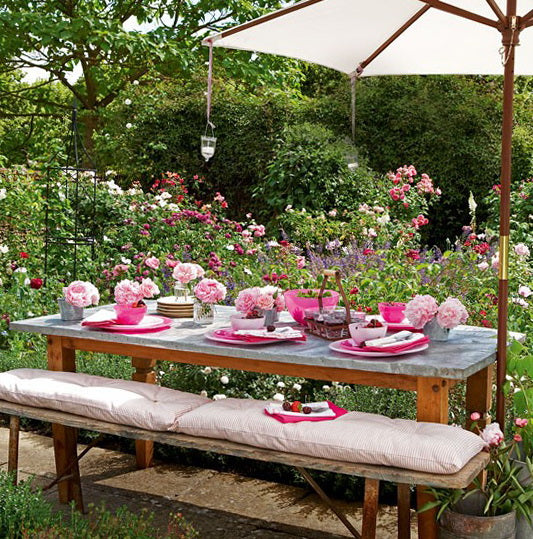 Outdoor garden dining table with sun shade and pink tableware