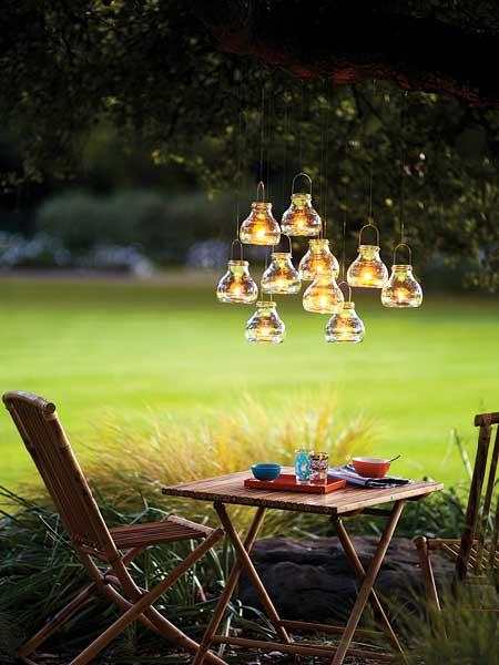 Glass bottles with tealights suspended from a tree, with wooden garden furniture underneath