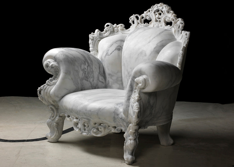 A white amr chair that looks like it's carved out of marble