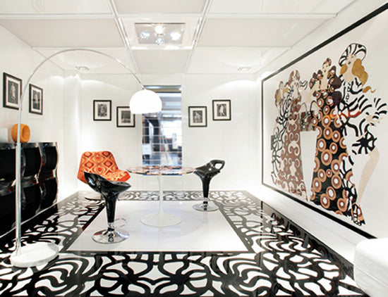 Black and white living space with small round table and black and orange swivel chairs
