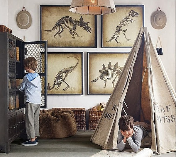 Wall art of dinosaur skeleton illustrations, with a teepee style tent in a kids bedroom