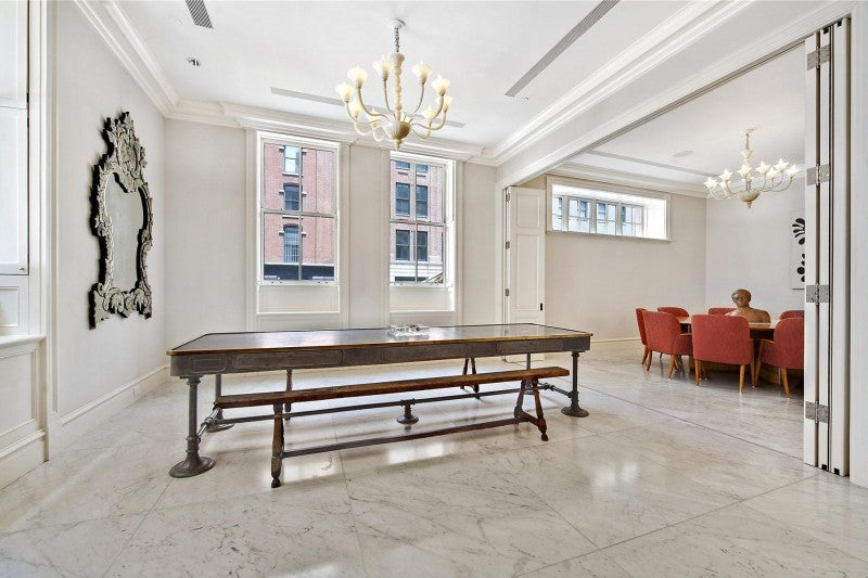 White marble flooring in a living room, with wooden table and ornate chandelier light fixture