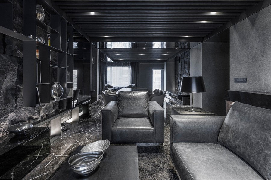 Black and grey living room with black furniture and black marble floors and walls