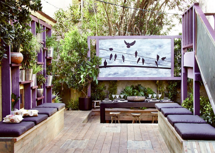 Wooden outdoor seating area with purple seat pads and purple planter shelves