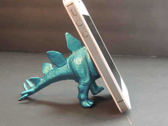 The back of a dinosaur as a phone stand, in blue