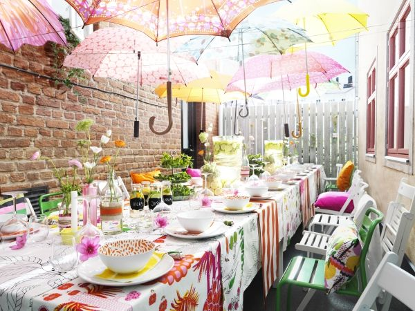 Quaint garden party with brightly coloured table cloths and bright umbrellas suspended overhead as a canopy