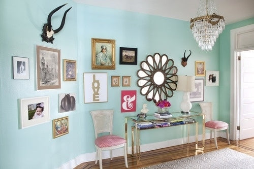 Light blue hall with various framed pictures and a mirror