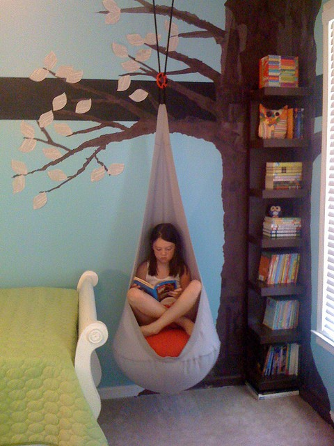 Young Girl Reading In A Hanging Hammock Chair, In Front Of A Tree Mural
